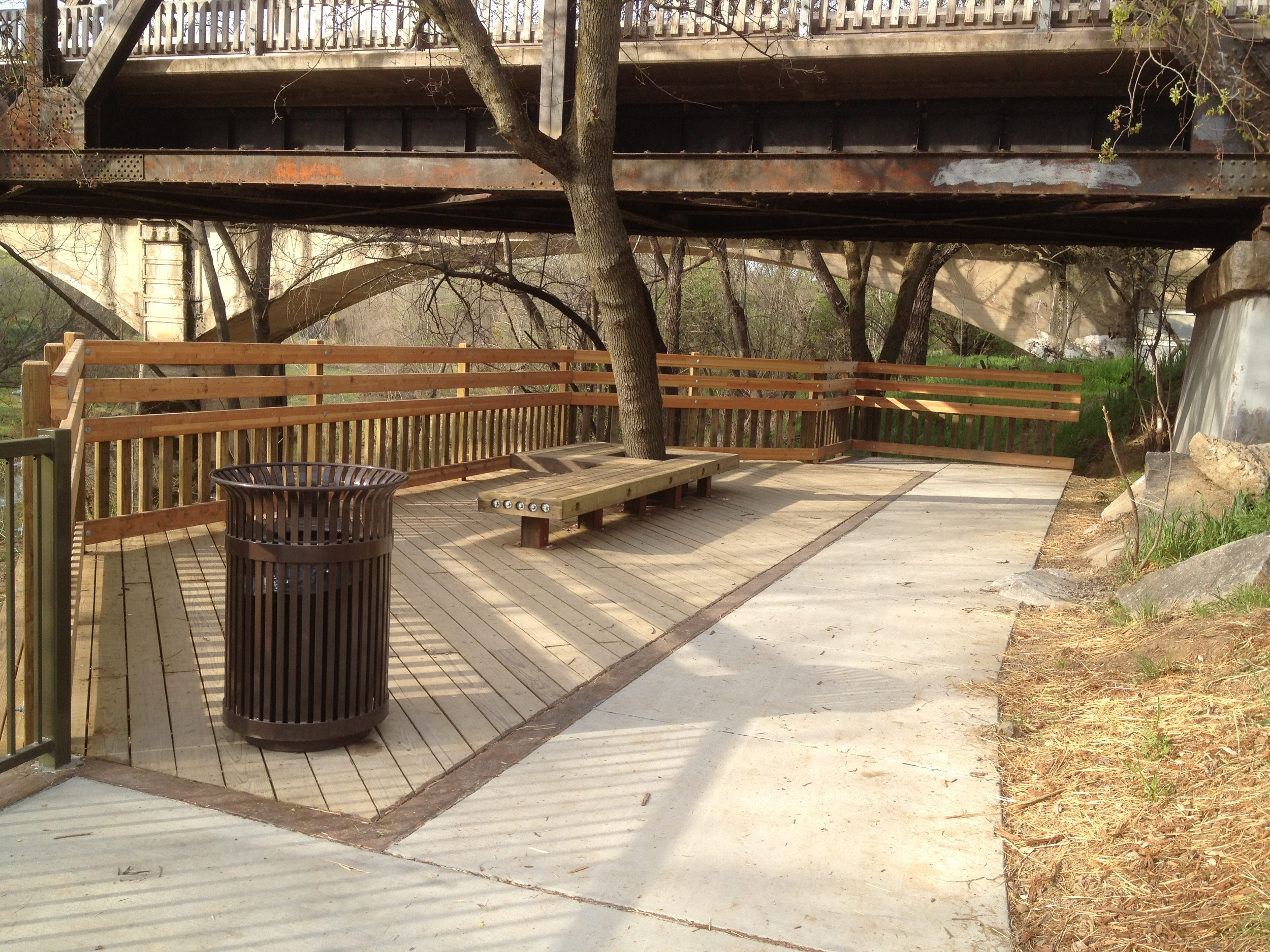 New overlook and benches below community center nestled partly under historic railcar pedestrian bridge
