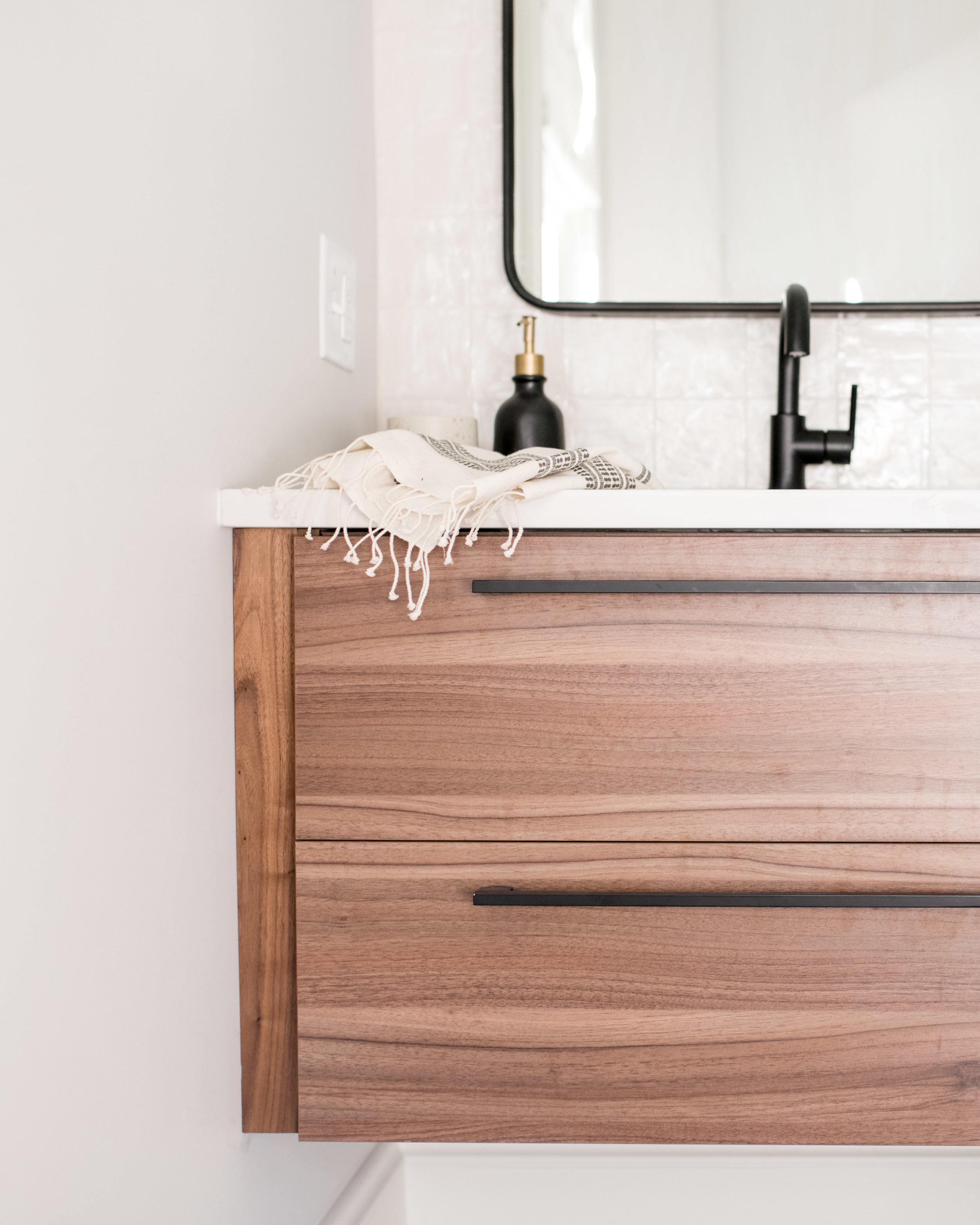 walnut floating vanity and black hardware