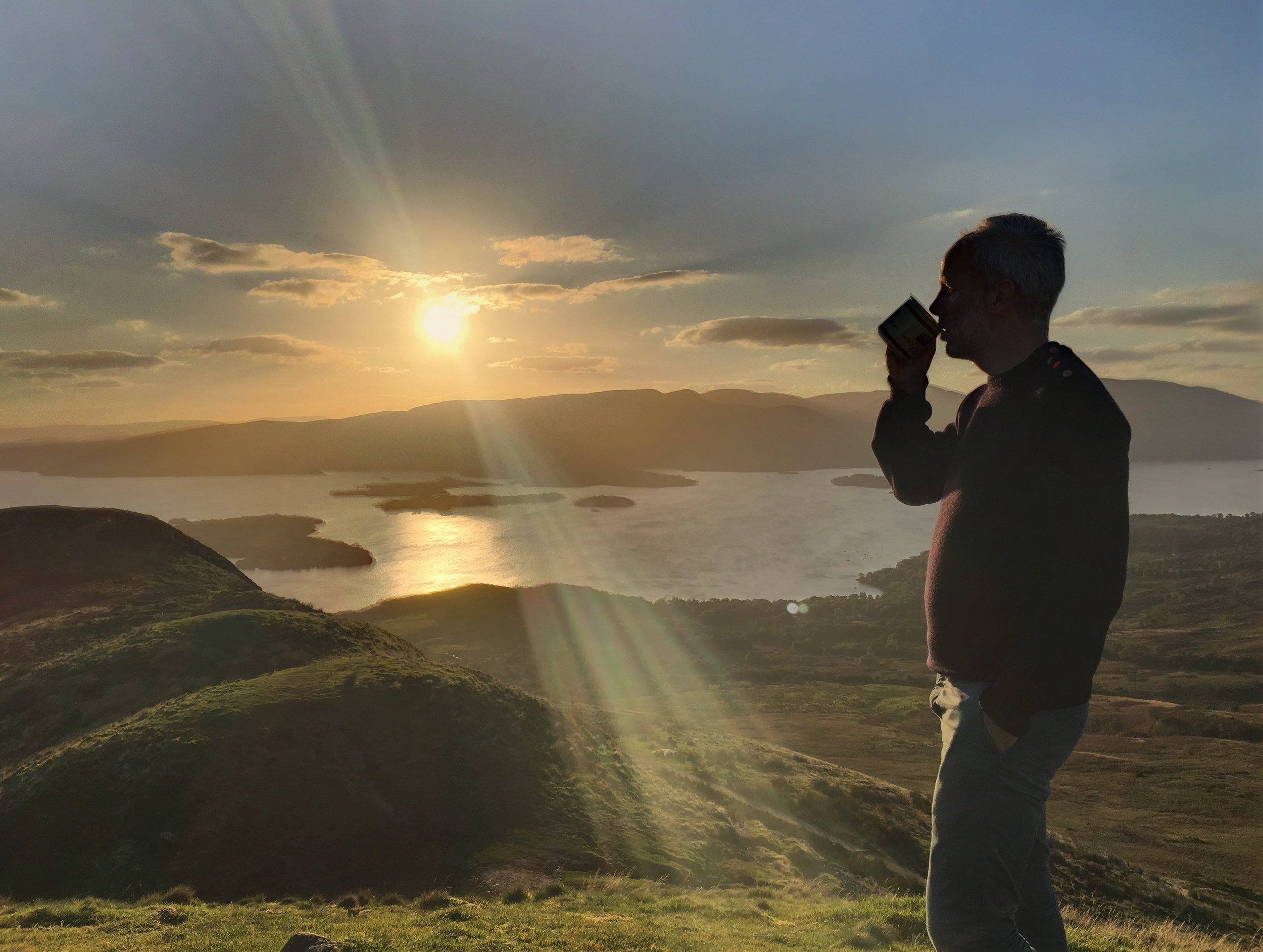 traveller enjoying whisky and a sunset