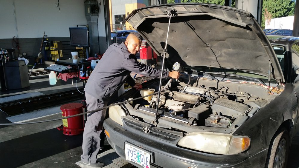 mechanic at Tigard Fast Lane Oil Change working on a car engine