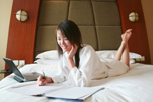 woman-on-bed-working-200-300