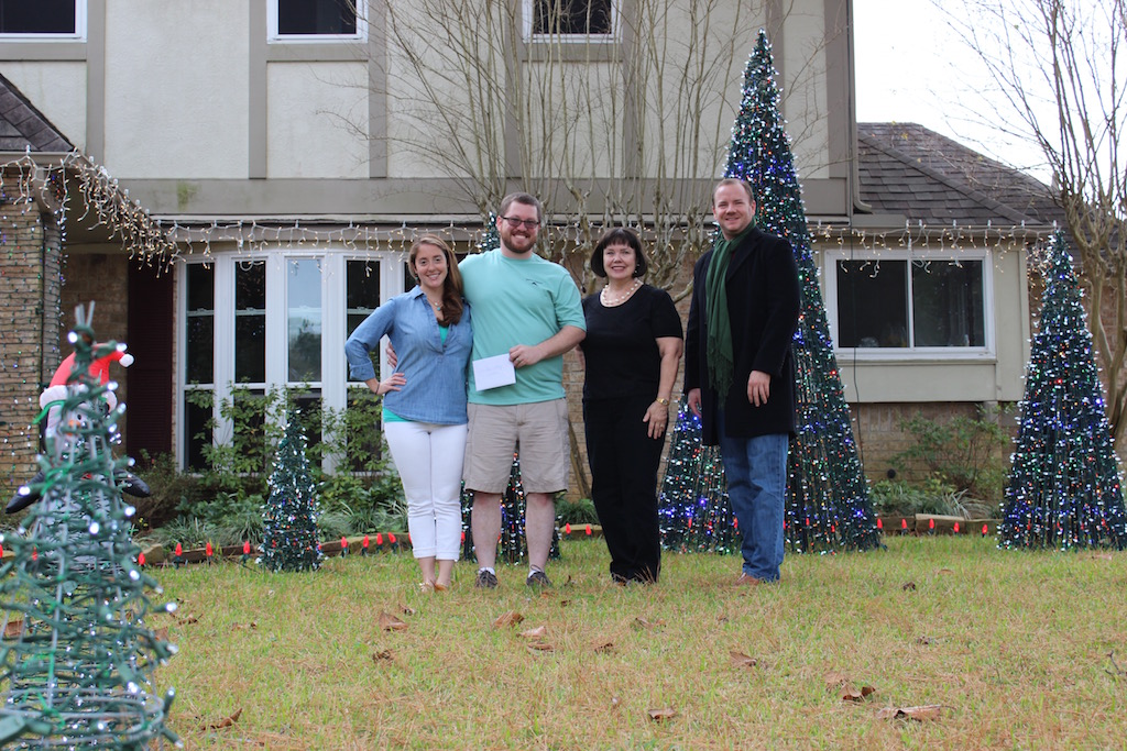 QVGC Holiday Light Committee members Linda Holder and Clay Cessna present awards to the homeowners.