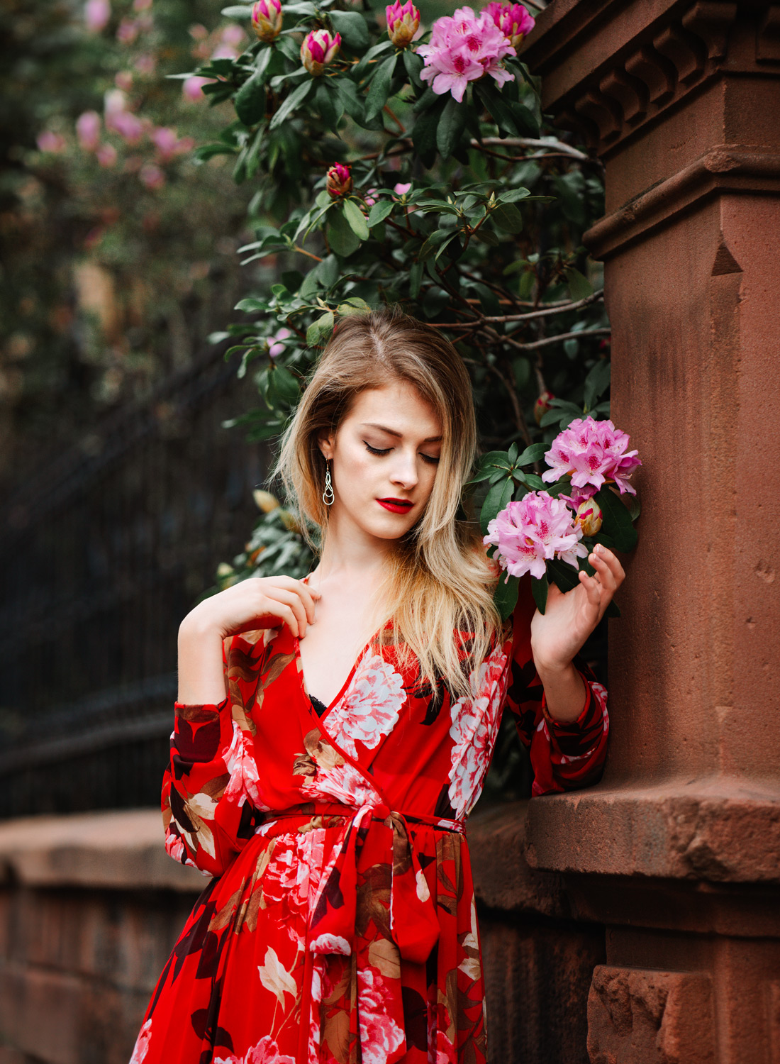 young blonde model woman in red summer dress and pink flowers in a high end fashion photo session in Kaiserslautern germany and ramstein landstuhl kmc area by portrait photographer sarah havens  junge frau in rotem sommerkleid in einem mode shooting in Kaiserslautern, Rheinland-pfalz.