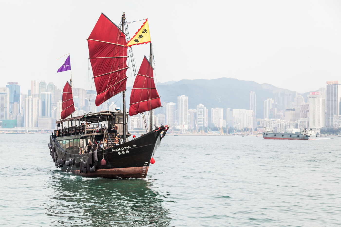 Aqua Luna - a red sail Chinese junk boat sailing through Hong Kong's Victoria Harbour.