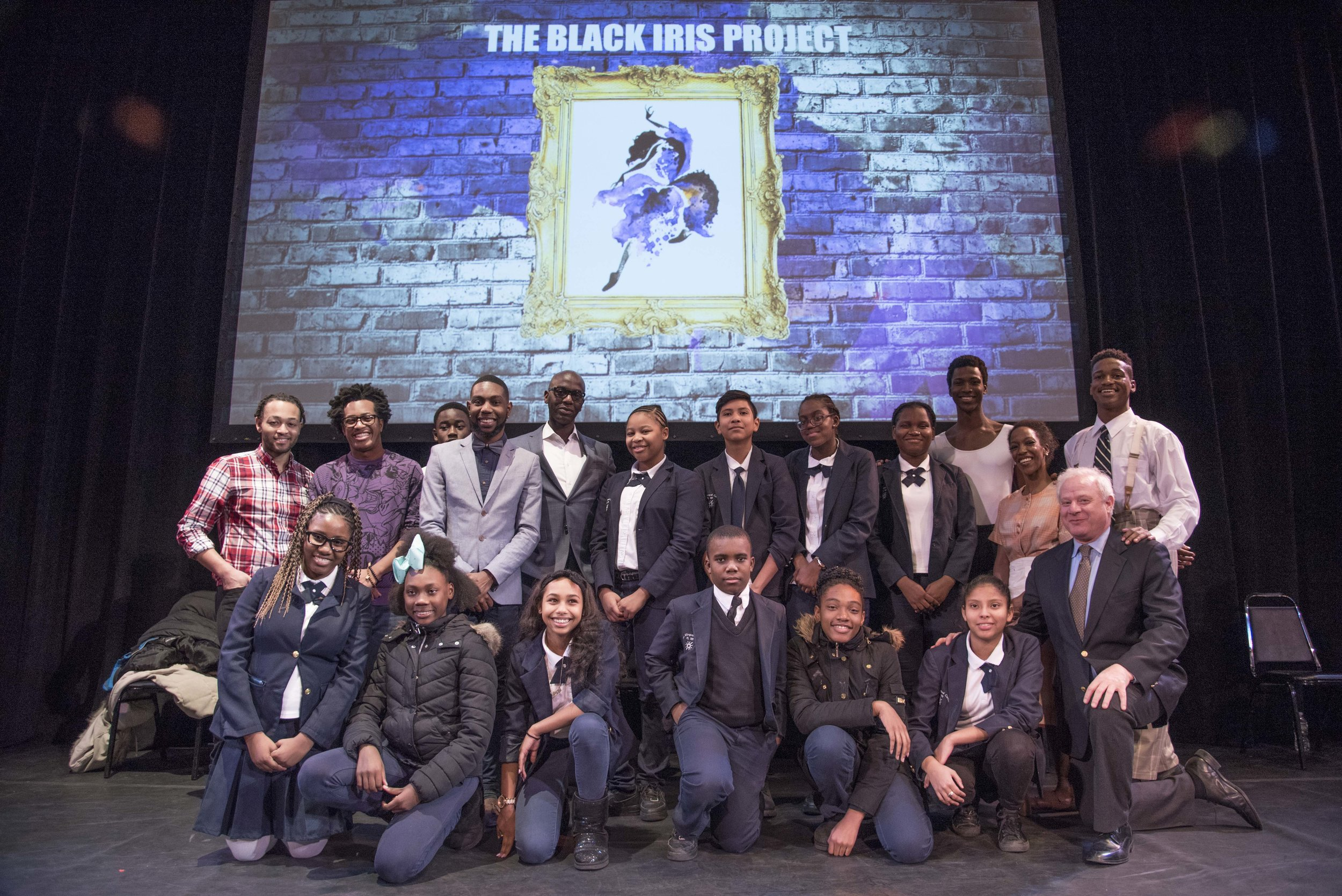 The Black Iris Project founder Jeremy McQueen (plaid shirt, left) Con Edison's Alton Murray (center, glasses) and Town Hall president Tom M. Wirtshafter (right, kneeling)  welcome students from P.S. 189 in Brooklyn to The Town Hall.