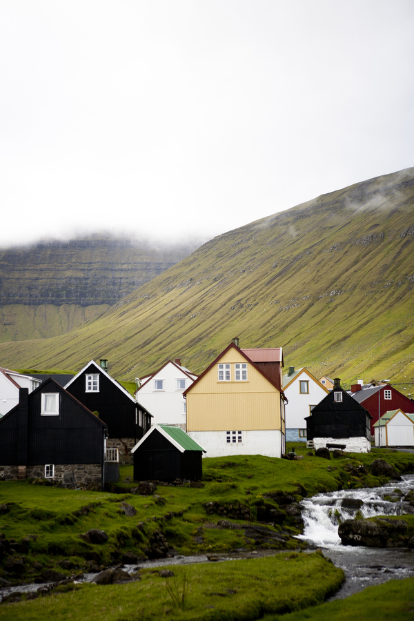 The small village of Gjógv is nestled in a valley in the mountains of the Faroe Islands. Many villages, such as this one, are home to no more than 100 people, often from the same family unit. This particular village has no grocery store or gas station — its only buildings that are not houses include an old church and an indoor fish farm.