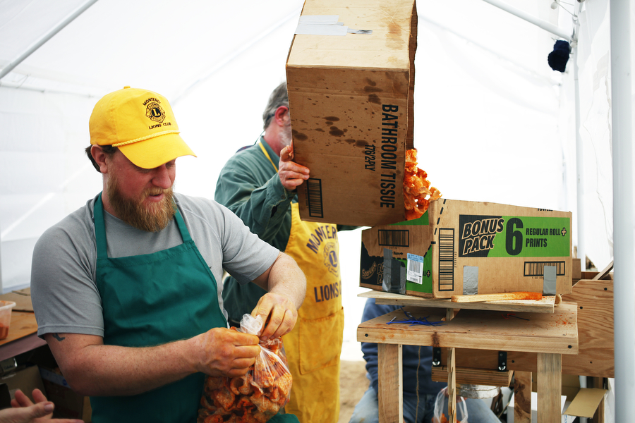 Todd Frye and Randy Richardson coat pork rinds in barbecue powder with the Monterey Lions Club on Saturday, March 8, 2014, during the Highland County Maple Festival in Monterey, Va.