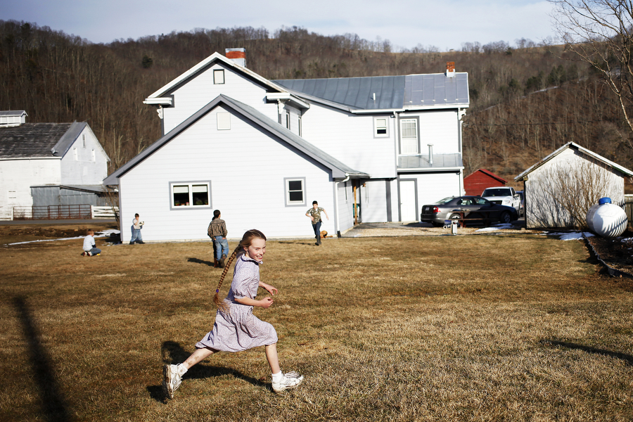 Jennifer Hartzler, 9, runs as she plays tag with friends and siblings behind the Sugar Tree Country Store on Saturday, March 8, 2014, during the Highland County Maple Festival in McDowell, Va. The families of the children were at the country store to sell maple ice cream and maple chicken as a part of the festival.