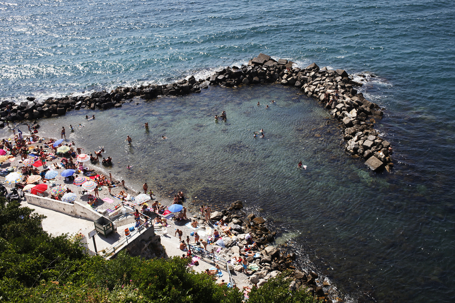 People swim in Stone Beach in the Mediterranean Sea on Sunday, July 6, 2014, in Sorrento.