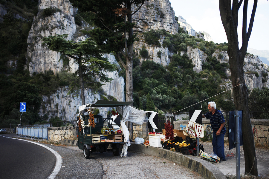 "A man sells produce, including grahita limones, or ""big lemons,"" on the side of the road leading on Tuesday, July 8, 2014, into Amalfi."
