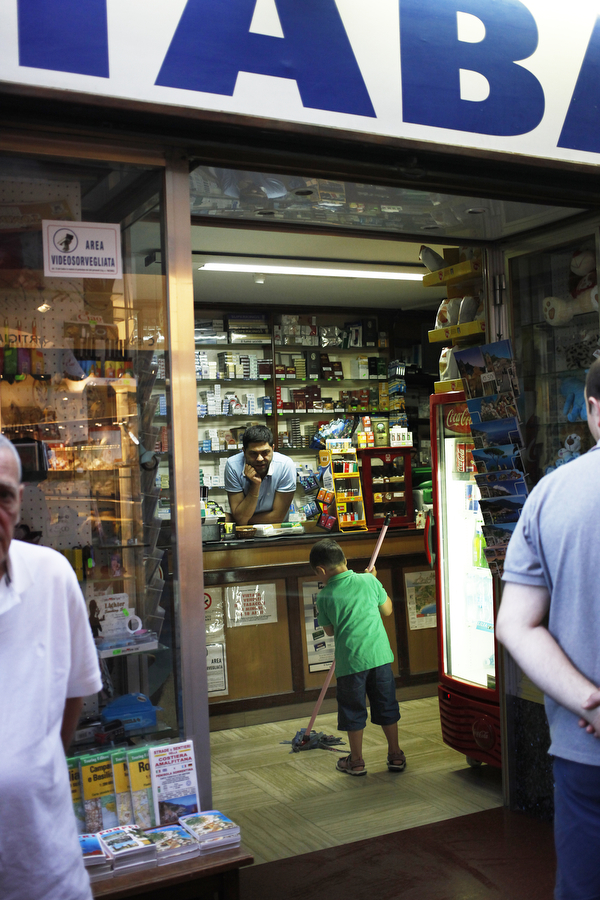 A boy mops up the floor of a tabacchi as the clerk looks on, laughing, on Wednesday, July 9, 2014, in Amalfi.