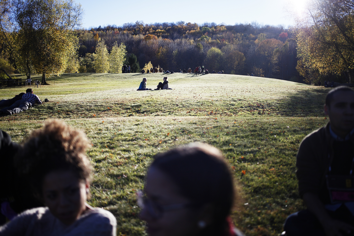 Students lay in the grass after turning in their assignments on a beautiful fall day in Jeffersonville, New York during the 27th Eddie Adams Workshop.