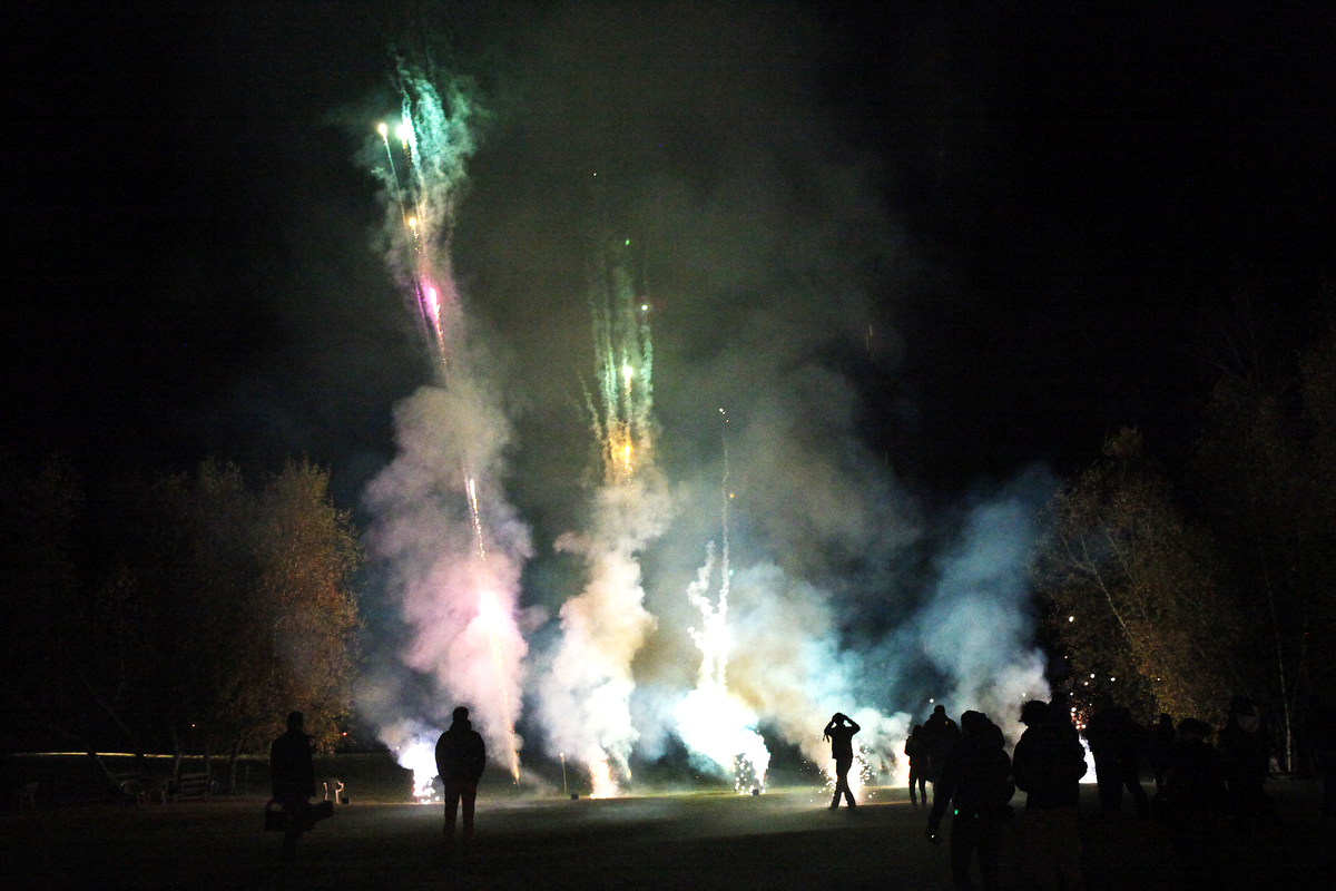 People gather around the fireworks during the bonfire at the 27th Eddie Adams Workshop.