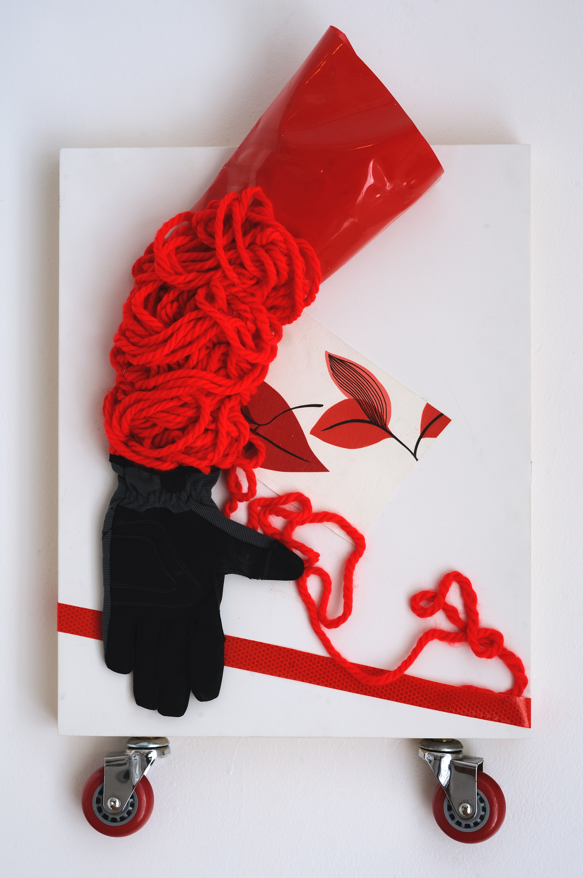 """Flying Wheels   Utility glove, vinyl, tape, wheel, yarn on wooden block  18""""x 14""""  $1,300  Click to enlarge   Inquire."""