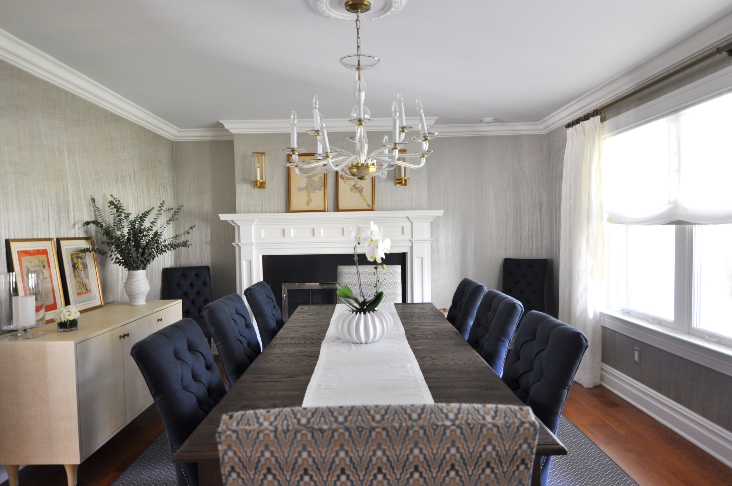 "CLASSIC DINING ROOM , Mamaroneck, NY: When the homeowners moved into their new dream home, they brought with them their dining table, chairs and chandelier, but envisioned a more finished, inspired space. The host chairs were reupholstered in a graphic navy blue and gold chevron that adds a fresh, yet classic look. Walls are covered in a vertical metallic ""moonstone"" colored wall-covering to add a sense of drama fitting for their vintage glass and brass chandelier.  Antique brass and glass hurricane sconces above the mantel add contemporary style and complement the vintage chandelier. Ivory linen sheer drapery and Roman shades for the large front window wall provide a light, easy style that counters the heavier dark wood table. An off-white  textured faux raffia buffet with brass knobs  sits on the chevron navy area rug ready to use as a serving area for the next dinner party."