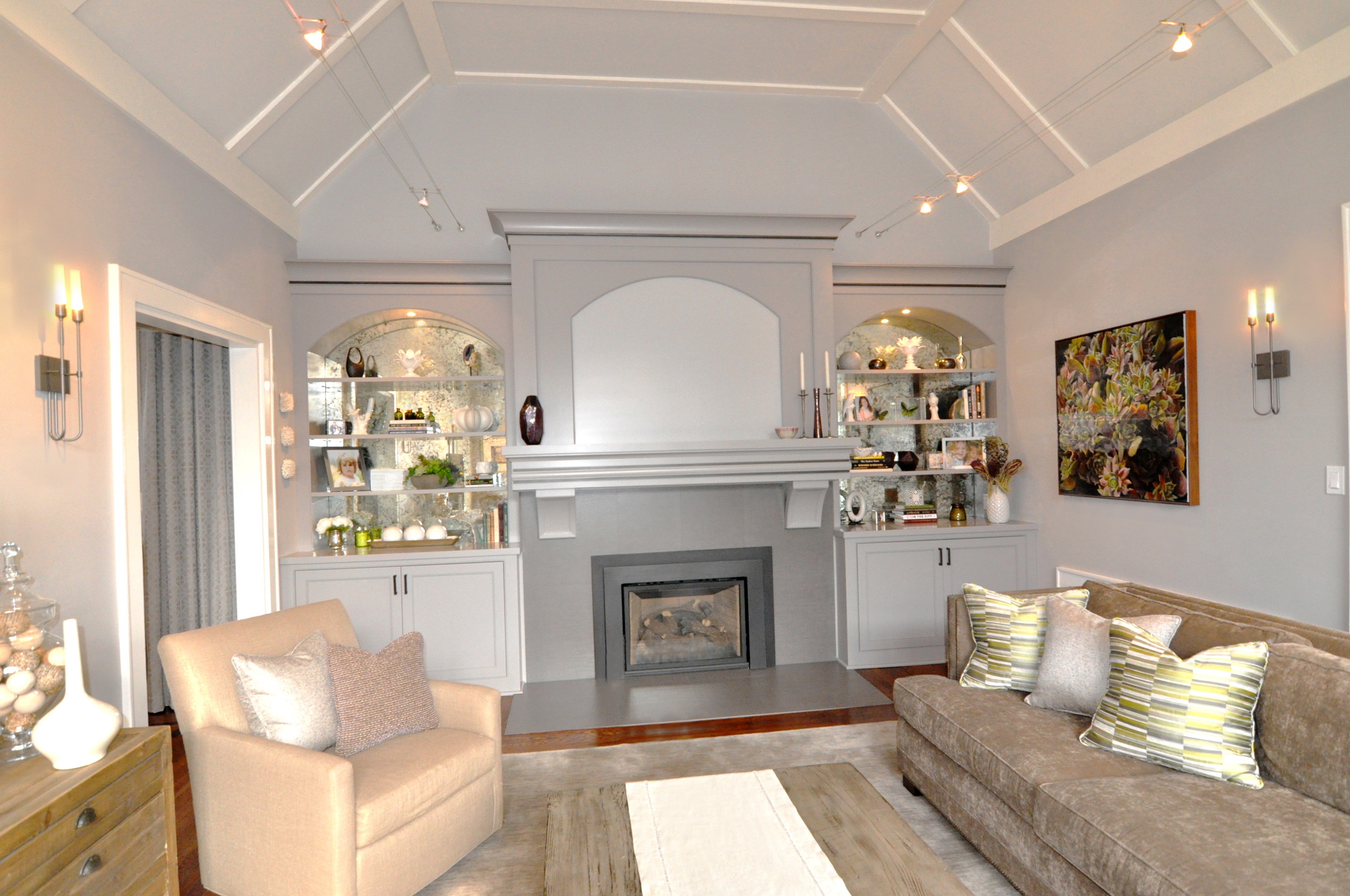 UNDERSTATED ELEGANT LIVING ROOM , Larchmont, NY: The custom-designed  fireplace, overmantel and built-in embraces the grandeur of the living room ceiling height. The existing hood was low, odd and awkward, unsuited for the charming home.  The  shelving mimics the arches of the large front window and the antiqued mirror back reflects their beauty, as well as natural light.  The new fireplace facade and hearth utilizes large format textured porcelain tiles to frame the new gas fireplace. Contemporary torch-like sconces honor the home's history and the homeowner's modern sensibility, while touches of chartreuse, spring-green and plum accessories are at home with the room's natural  hues.