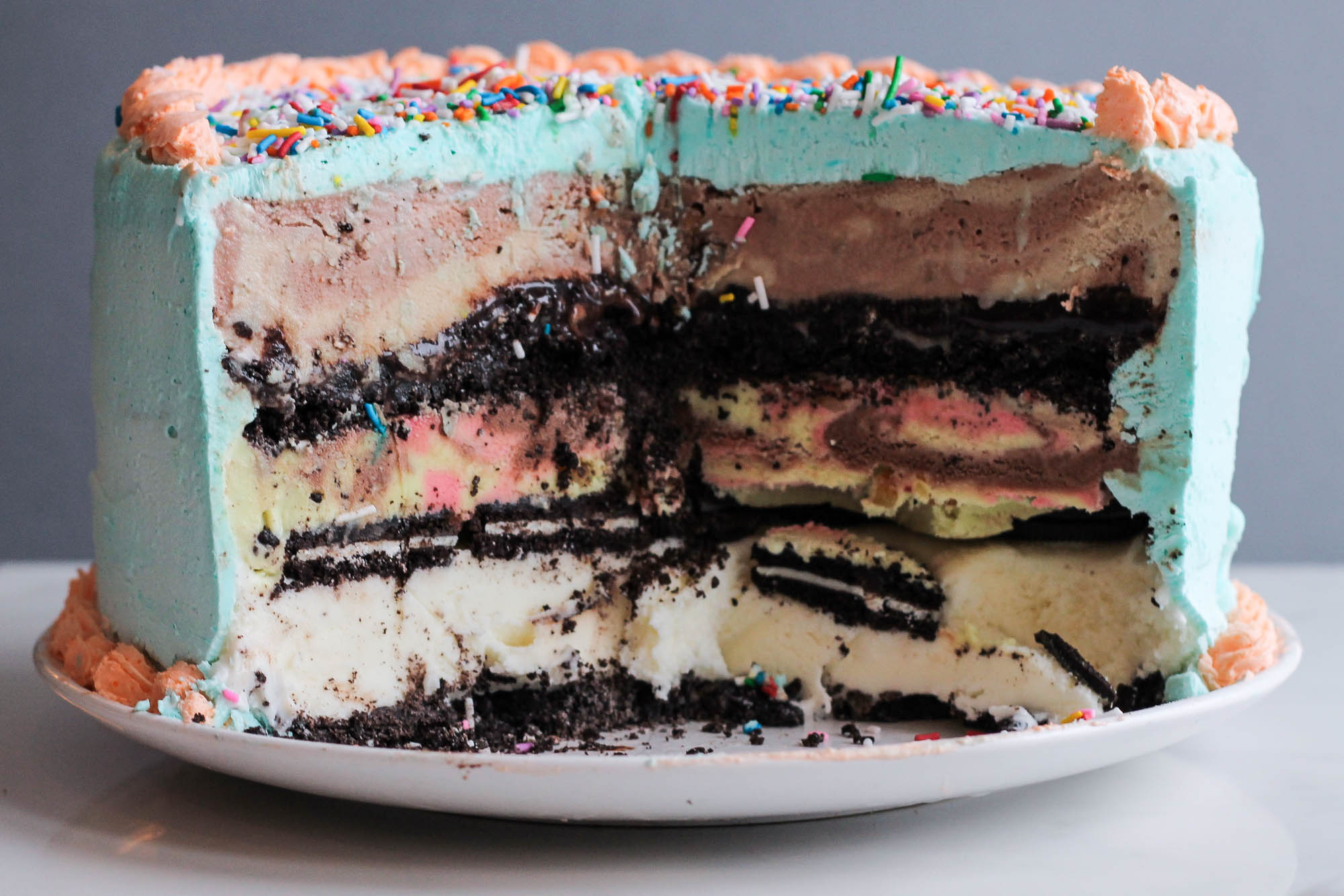 3 Layer Ice Cream Cake || A Dairy Queen inspired homemade ice cream cake recipe for all your birthday needs! This party dessert is loaded with three ice creams (chocolate hazelnut, vanilla + spumoni) with crunchy oreo + fudge layers. Topped with a whipped cream frosting. || creamandhoney.ca