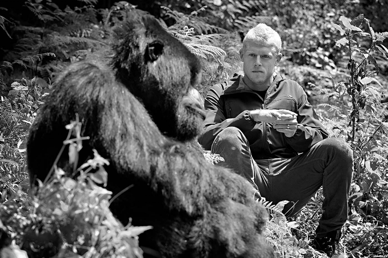 Portrait of Mick Fanning sitting with a silverback gorilla in the jungle from the book 'Adventures in Light' by Ted Grambeau.