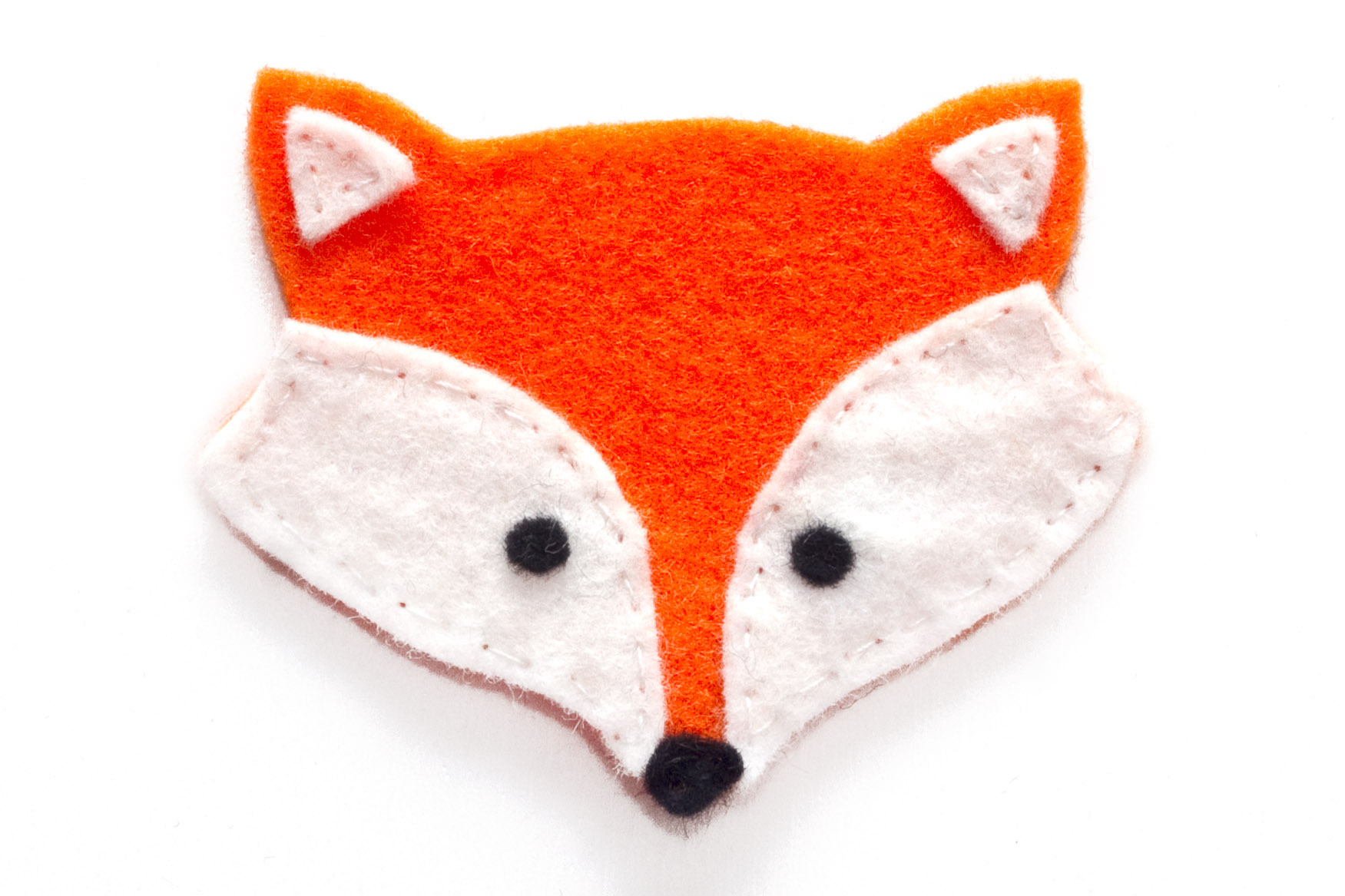 Step 2. Sew the black circles onto the white felt using the black cotton. Then sew all of the white felt pieces onto one of the orange felt shapes using white cotton. Then sew the black nose on with black cotton.