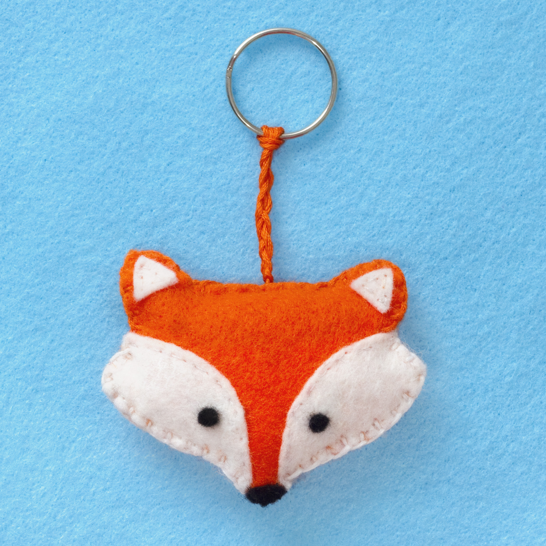 Step 3. Stitch the two orange pieces of felt together using a blanket stitch. Start with the top and use orange embroidery thread over the orange felt. Use the white embroidery cord over the white felt. Just before you reach the end, fill the fox with stuffing. Finally, plait some orange embroidery thread and use it to attach the keyring to the fox!  Subscribe to my  newsletter to receive fun craft ideas weekly!