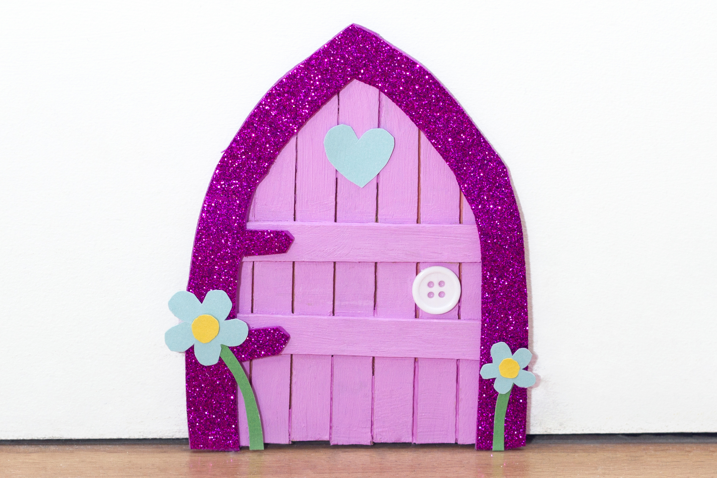 Step 7  Glue the heart and flower card shapes onto the fairy door and you're finished! Place onto a skirting board in your home for the fairies to come and go.  Subscribe to my  newsletter  to receive fun craft ideas weekly!  Please note: this blog post contains affiliate links, however all opinions are my own and I only link to products that I personally use and recommend.  Here's a video showing you how to make this DIY fairy door craft.  Subscribe to my youtube channel  for more crafty videos!