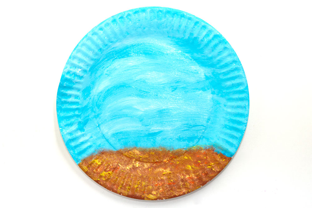 Step 1  Use the brown/orange/yellow colours to paint the stony floor of the fishbowl. Then use the blue paint to fill in the rest of the paper plate to create the water.