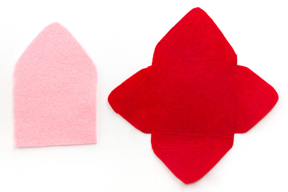 Step 1  Cut out the shapes shown in the photo above. They can be any size you like - I cut the red piece to about 16cm wide and that made an envelope that was approximately 10cm wide. So if you want it to be a bit bigger then cut these shapes slightly bigger! Make sure the pink felt shape is the same size as the upper triangle and middle section of the red piece of felt.