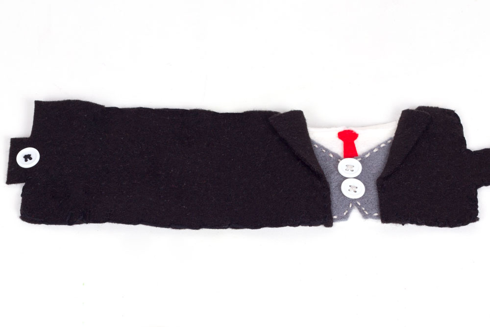 Step 3:  Using the black thread, sew the two black pieces of felt either side of the grey, about 1cm away from the buttons. Cut a button hole in the black felt on the right hand side, and sew a button onto the left hand side.