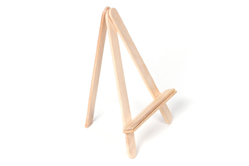 Step 2:  Get another lolly stick and trim the curved edge off of the bottom with the scissors. Then glue the remaining curved edge of the stick to the top of the triangular shape you made in step 1. This will create an easel shape that stands up on its own.