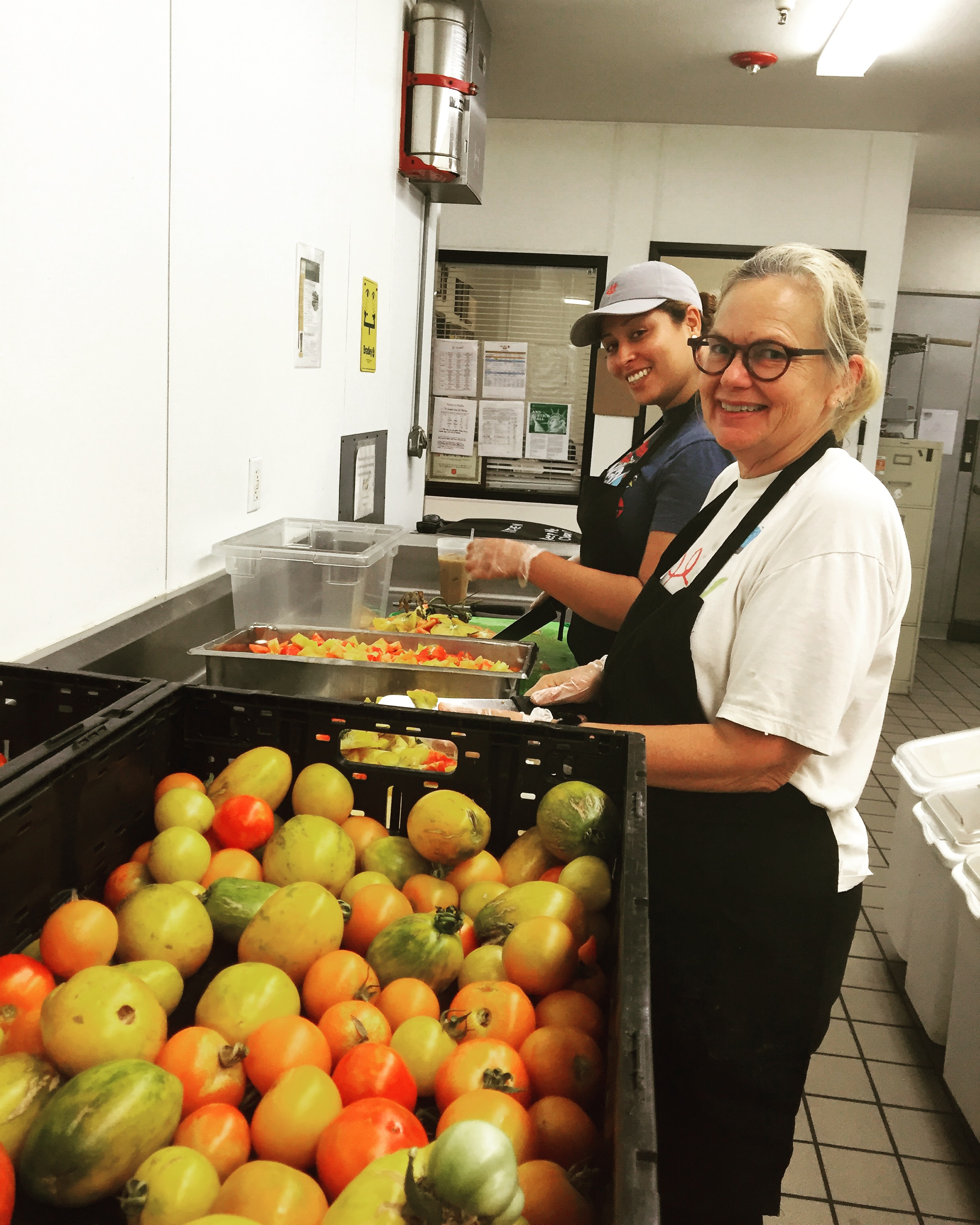 Mary and kitchen staff member slicing tomatoes.
