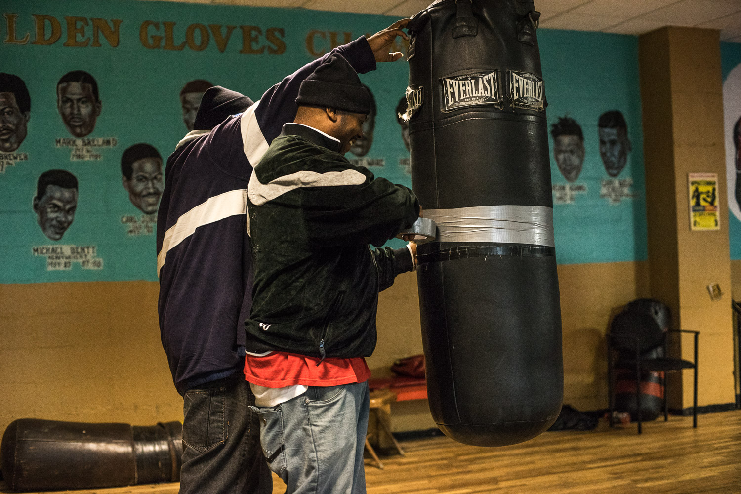 """Nate Boyd (50) puts strong insulation tape around a splitting punch bag. Situated in an economically disadvantaged area, maintaining, heating and opening the gym is a constant struggle. """"I'm tired man. Everybody's tired"""", says Nate Boyd (50), head coach at the boxing gym."""