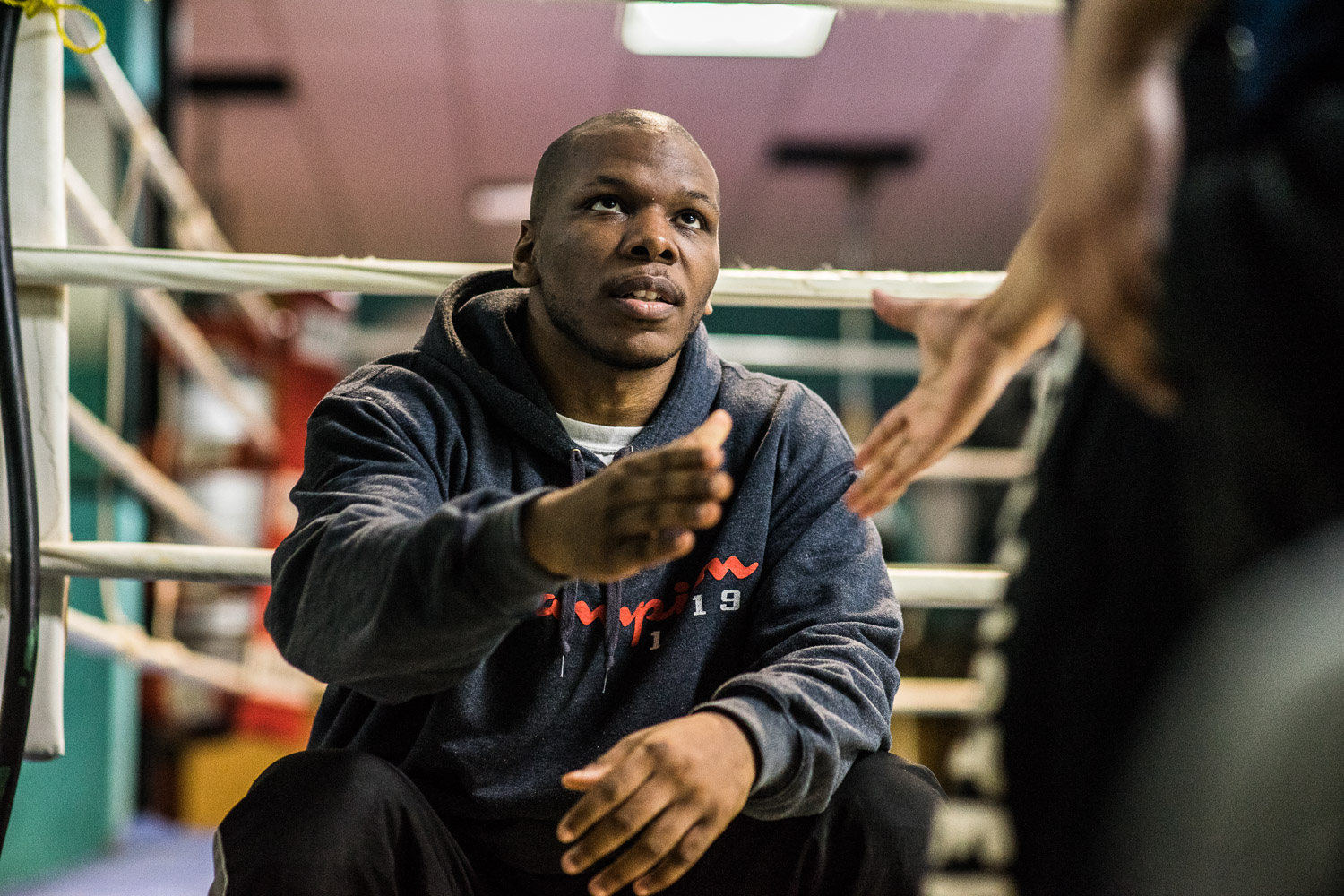 """""""Everyone is welcome here, no matter what skin color you are"""". Dan Mason (26) shakes hands with another boxer."""