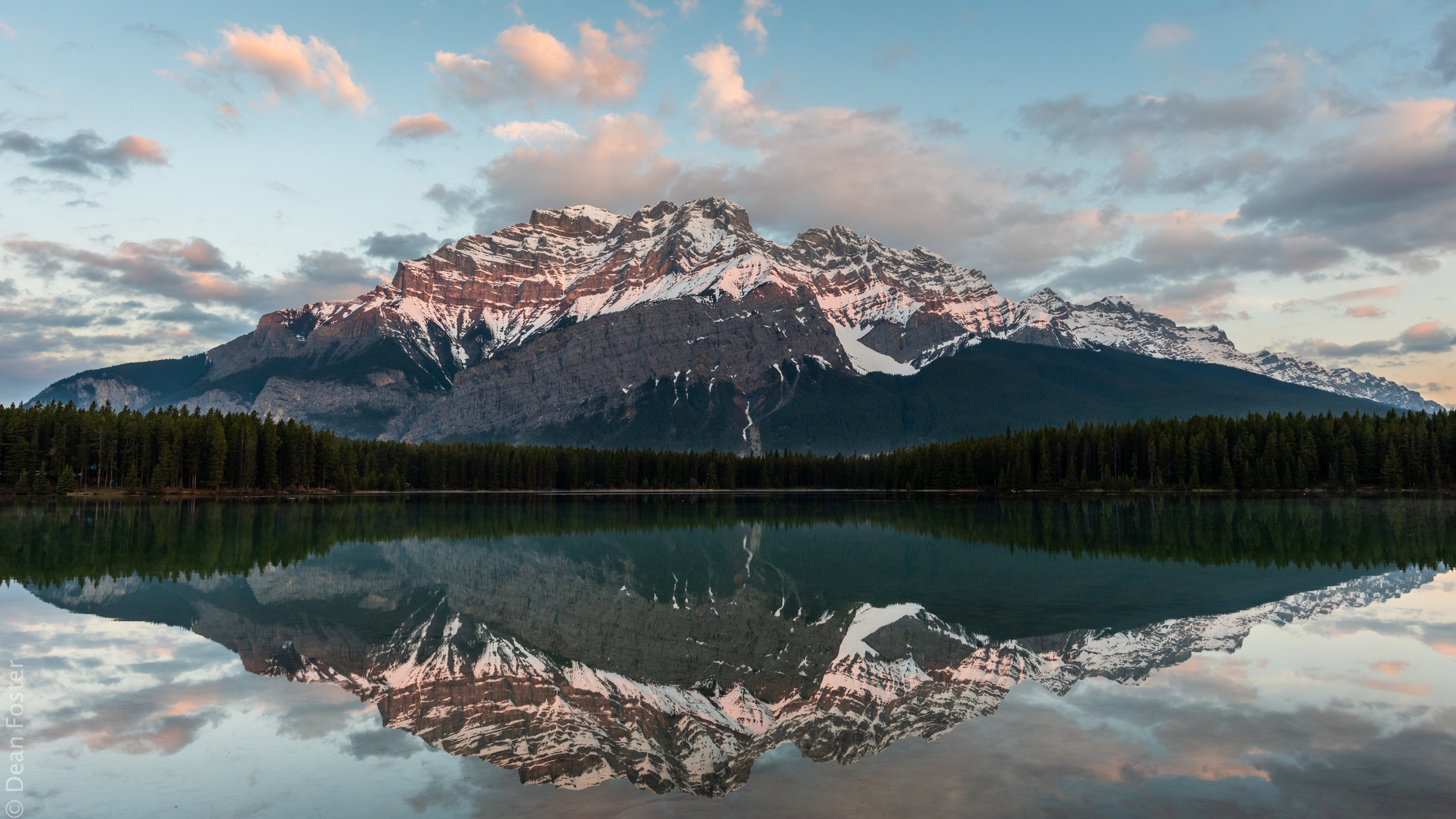 Cascade Mountain reflects in Two Jack Lake as the sun rises