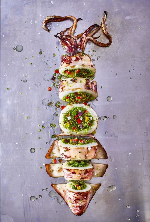 Calamari ripieni - Ingredienti per 4 persone:8 calamari2 fette di pane (senza glutine se è presente ospite celiaco)40 gr di Parmigiano2 uova2 spicchi d'aglio1 bicchiere di vino biancoSale q.b.Pepe q.b.OlioPrezzemolo q.b.Olive nere q.b.Capperi q.b.