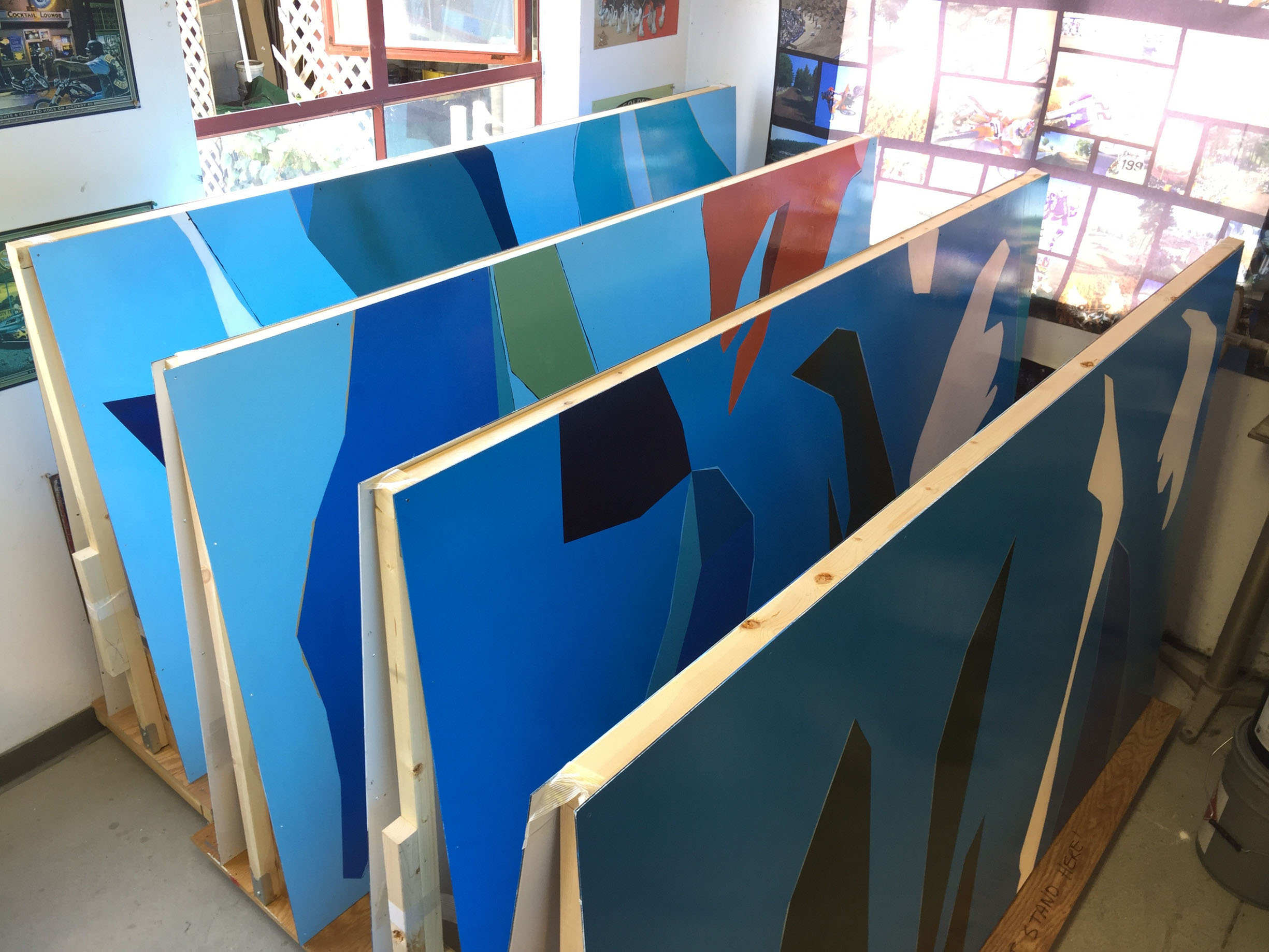 Mural panels resting between coats of varnish