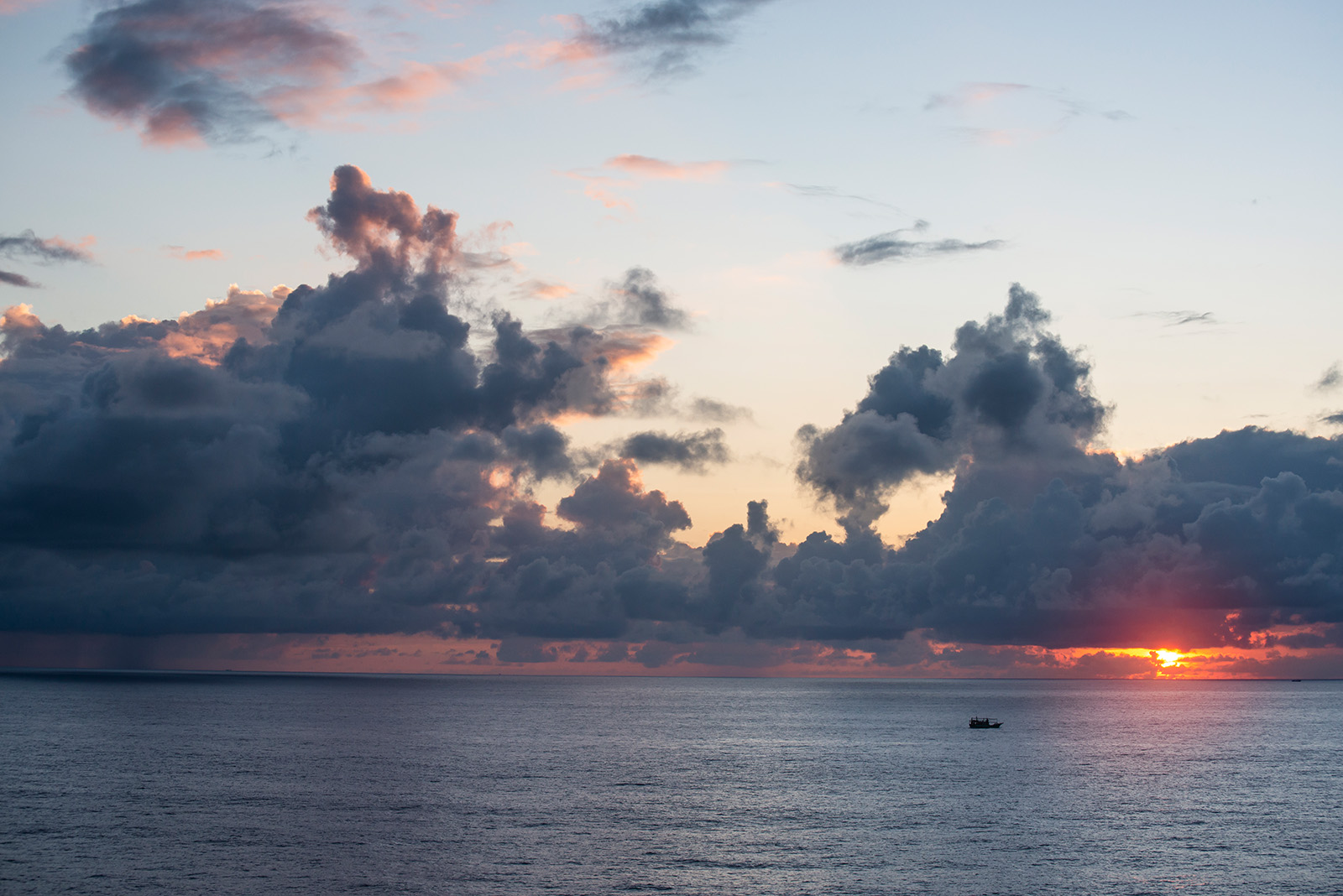 色彩就是在一瞬间迸发出来,雨云虽然依旧浓厚,但是无法阻挡太阳把颜料洒向空中。恰好有渔船经过,多了一些生动。