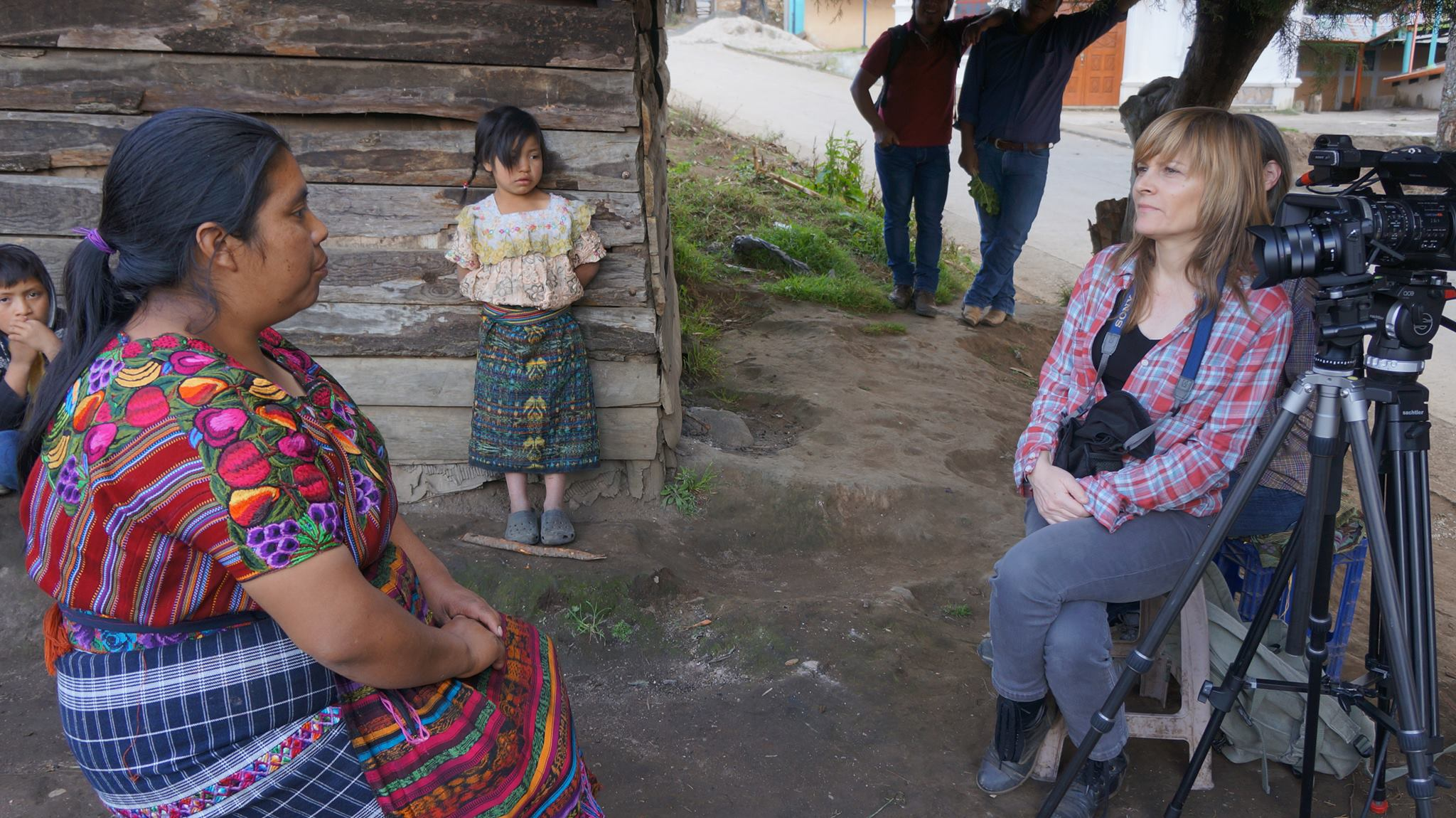 Jody Santos interviewing an indigenous woman in Guatemala as the woman's daughter looks on