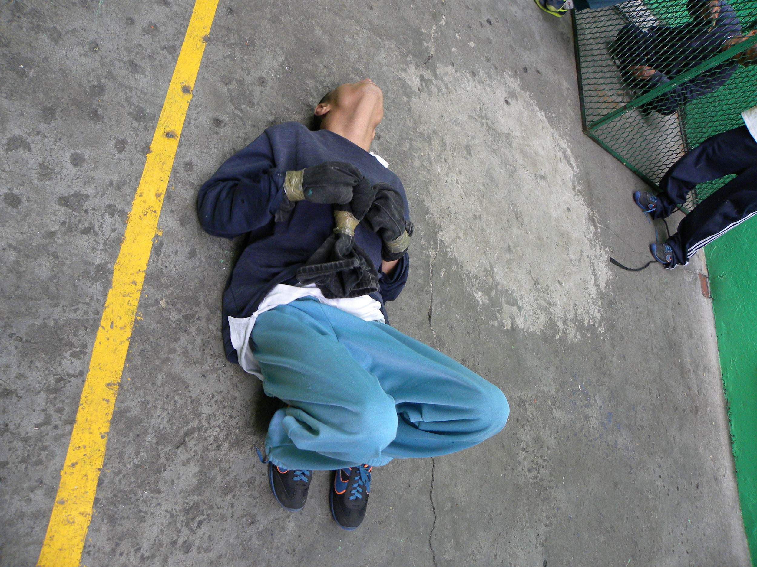 A young man whose hands are bound and duct-taped at a facility in Mexico