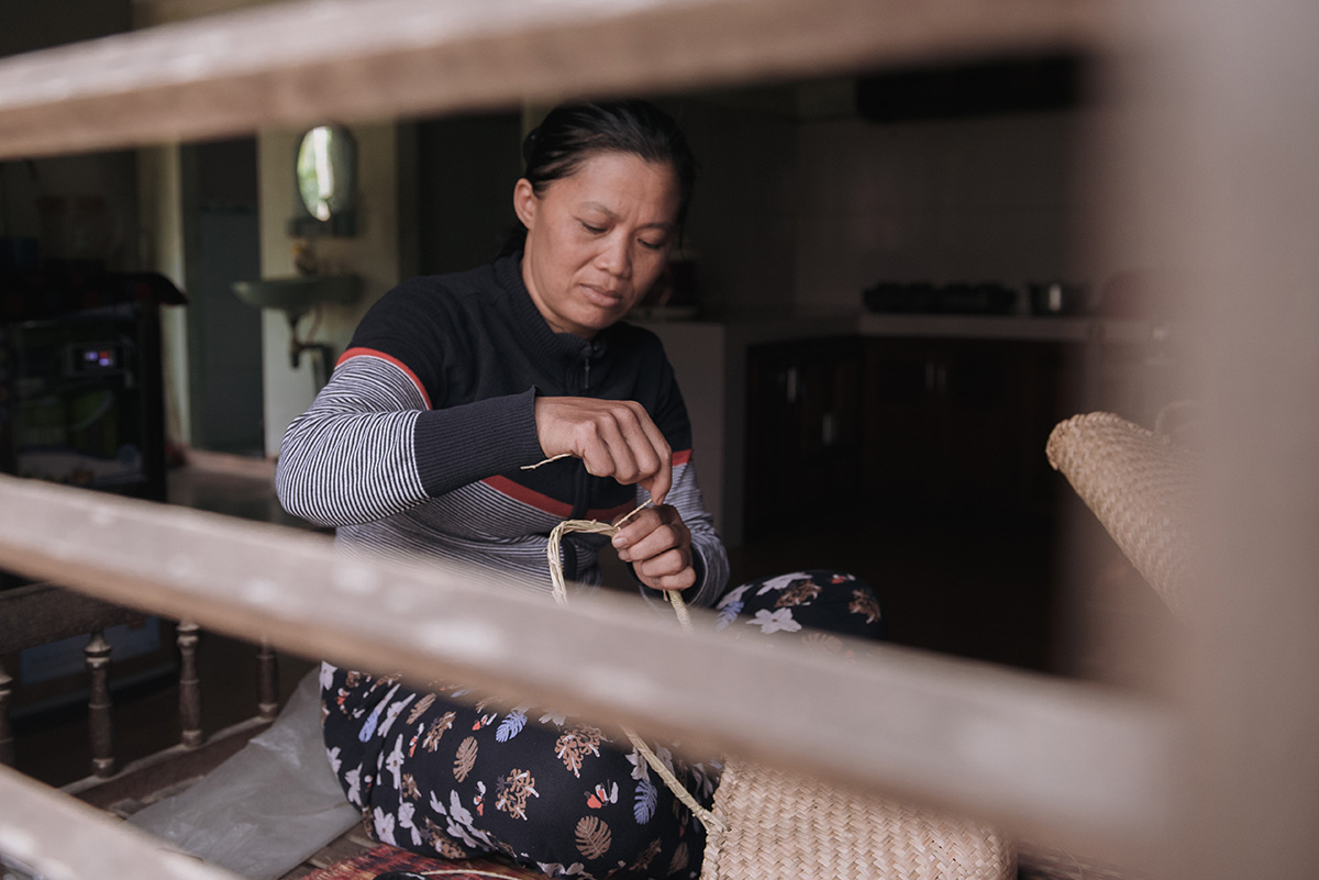 Hien working on one of the first prototype straw-weave bags.  Photography by Ody.