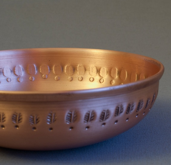 The  LEVANTE Copper Bowl Tealight Holde r with custom leaf-like motif.
