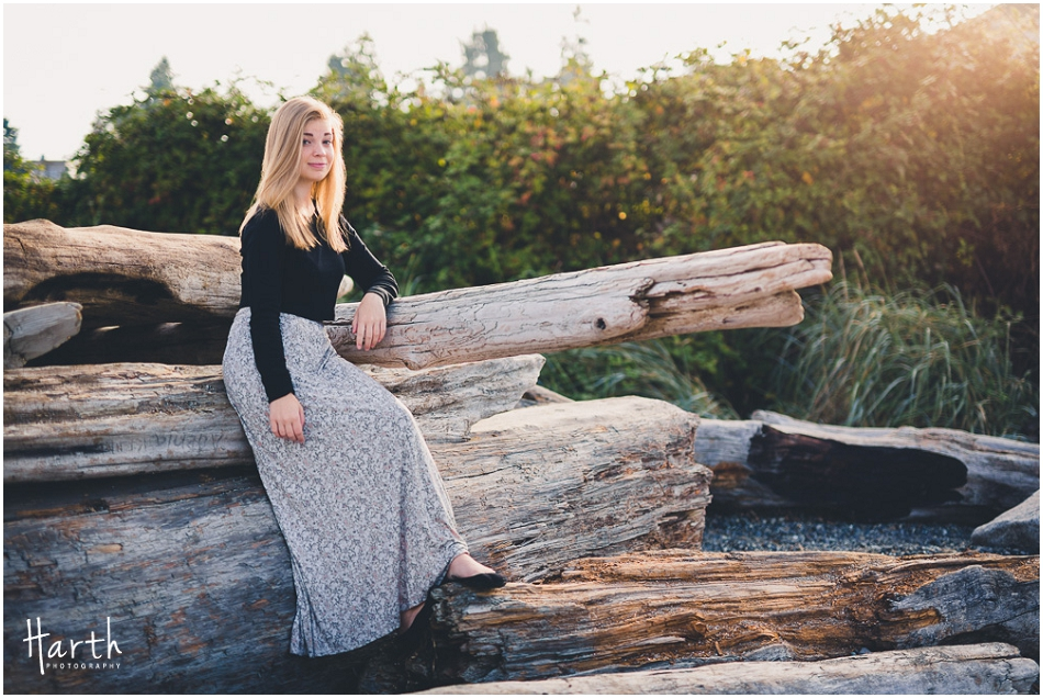 Senior sitting on beach logs during sunrise