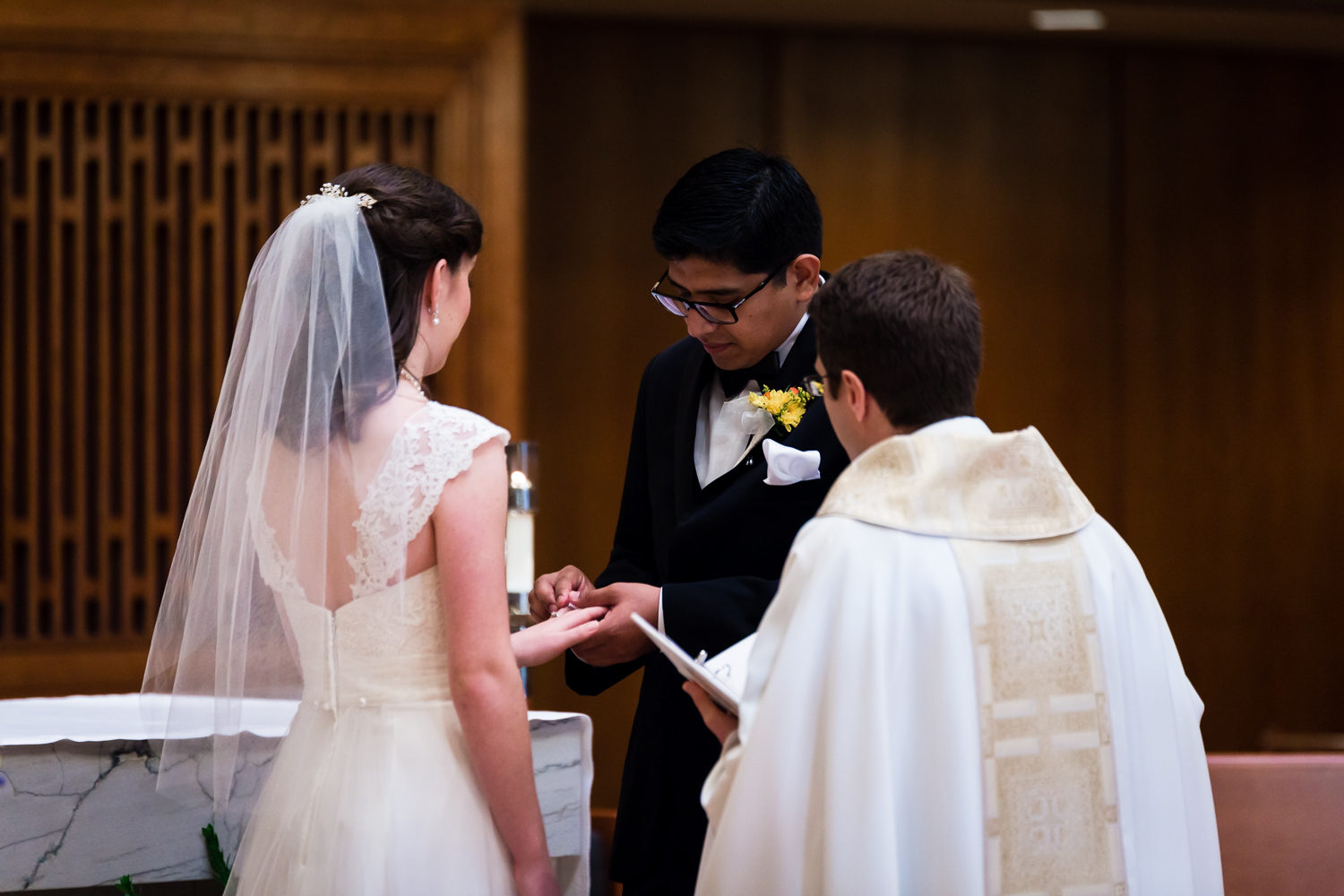 Groom putting wedding ring on the bride.