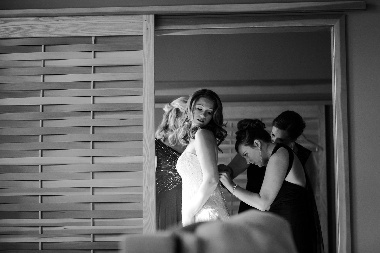 Bridesmaid helps with brides wedding dress