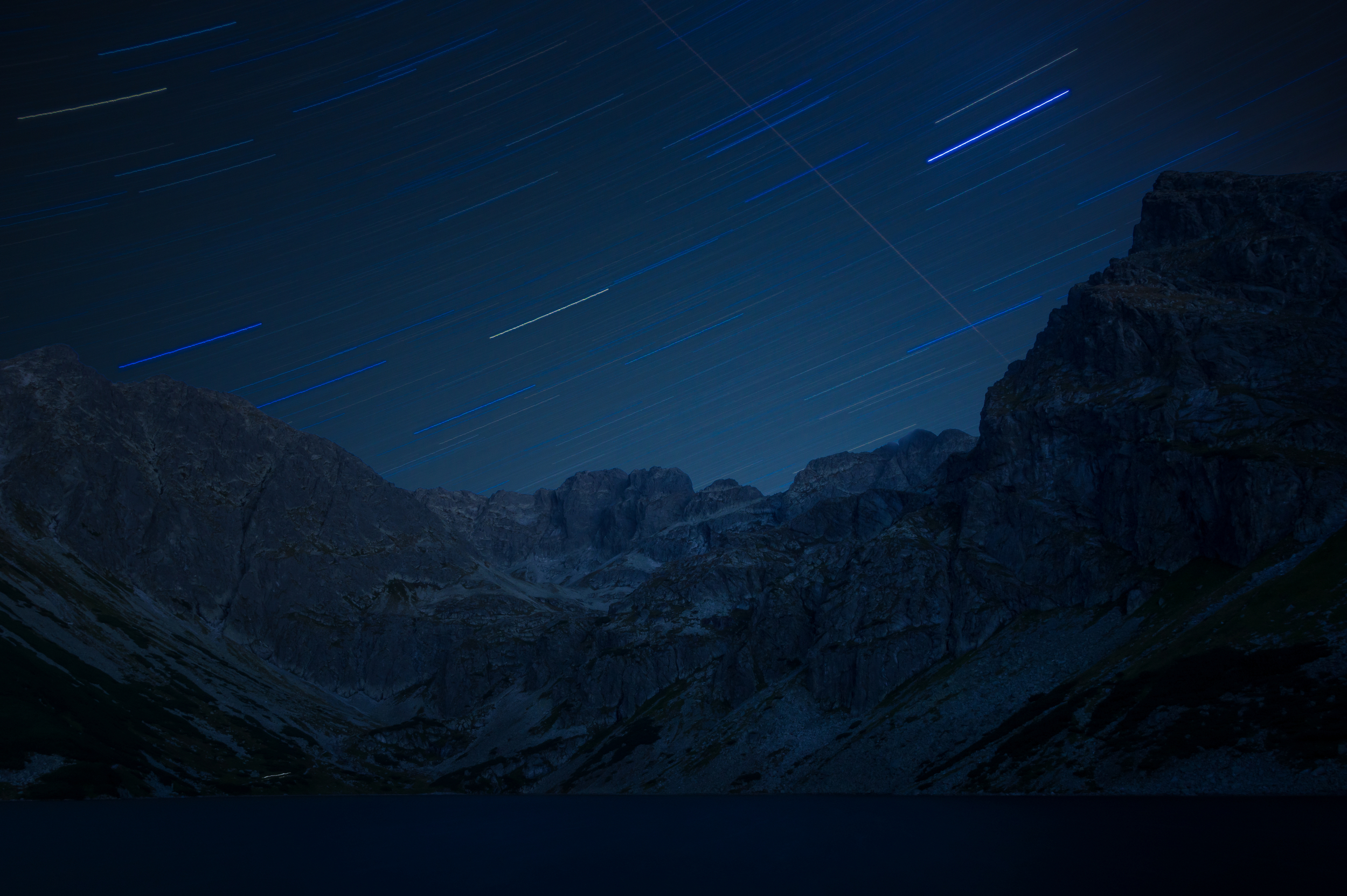 Star trails over Tatras and the last returning mountaineer with Headlamp