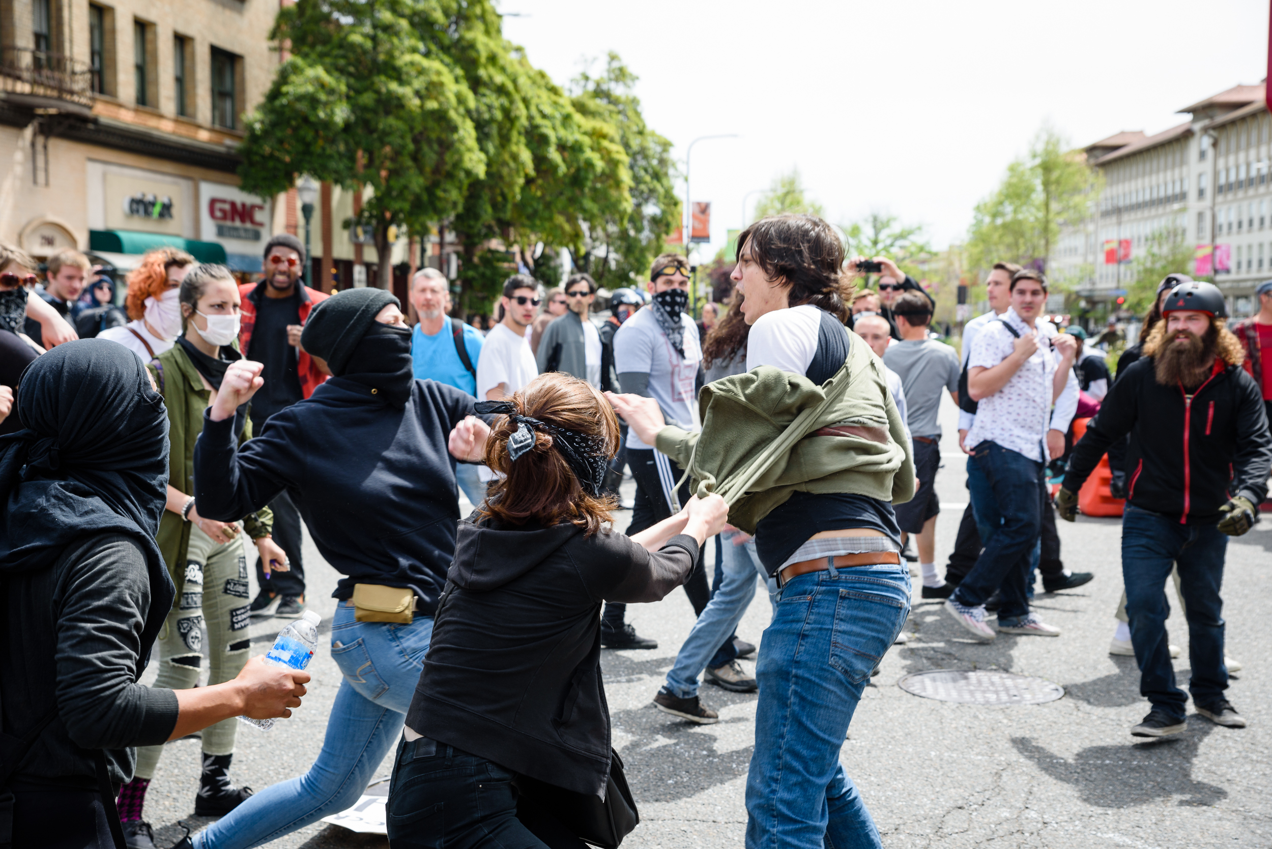 "'Antifa' or Anti-fascists employ black bloc tactics during a Free Speech rally in Berkeley, CA,  Here two of them are in a confrontation with a man who was holding a sign that read ""Hate Speech is Free Speech"" before it was stolen."
