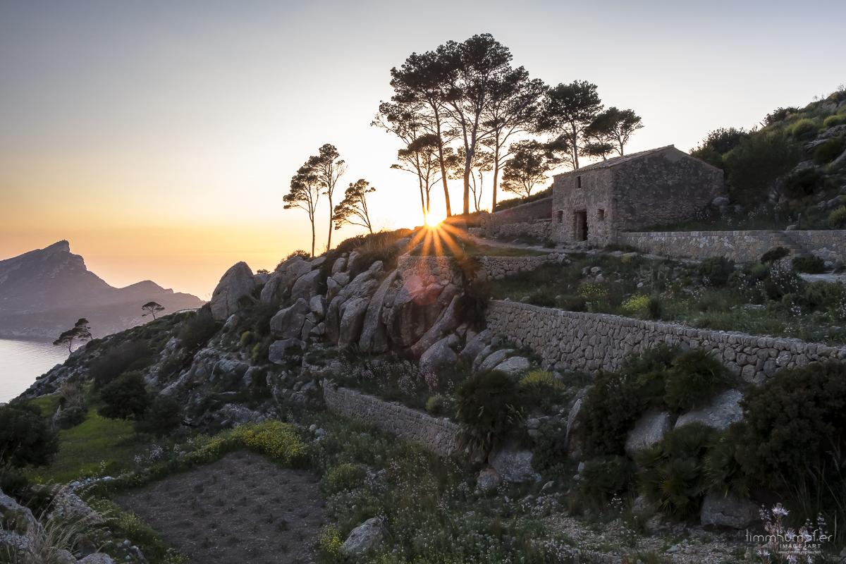 """Die Sonne verschwindet hinter den Hängen des Trappistenklosters """"La Trapa""""."""