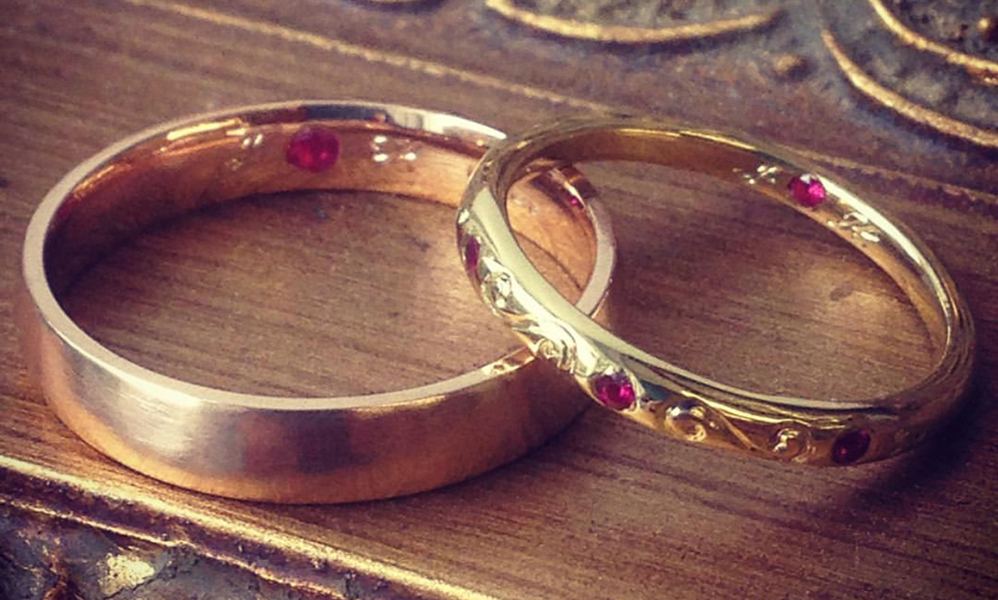 18 Carat Rose Gold & Yellow Gold Wedding Set With Ruby - Two beautiful hand crafted wedding bands. Ruby is a gemstone well known for love. We hand carved their initials on each side of the ruby inside the bands, joining them in unison. Finished with Victorian style hand carved engraving for Her.