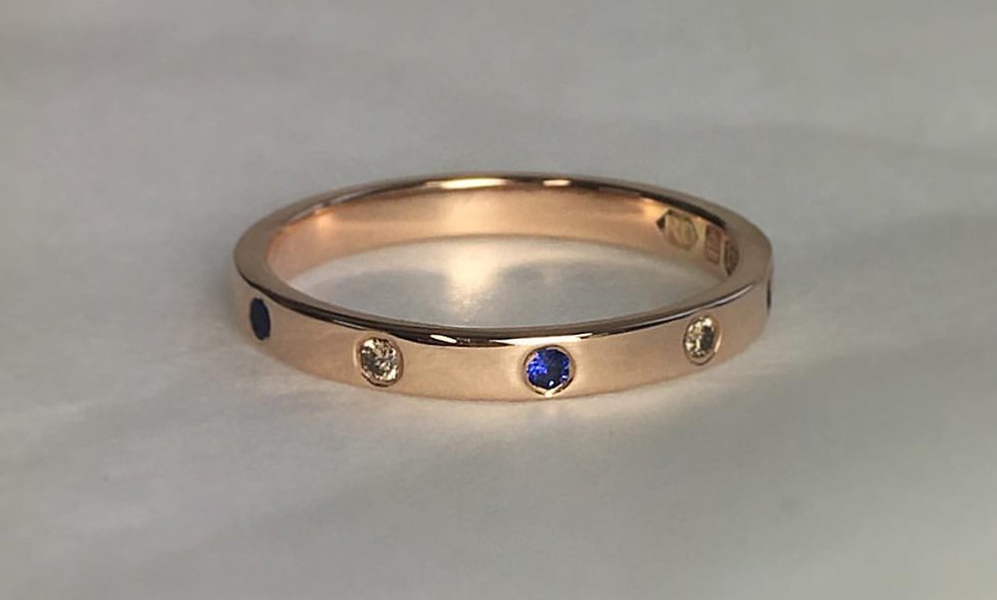 "18 Carat Rose Gold Wedding Band Set With Blue Sapphire & Champagne Diamonds - Stylish and understated wedding band. Simple is always best. We love this combination of precious gemstones. Inspired by the cosmos, gazing up at the sky searching for shooting stars. Magical.""Such a beautiful surprise. My boyfriend of 5 years finally put a ring on it. I think he knew that any old shop bought ring just wouldn't do, and knew of Rosie through a mutual friend. He told me they met up several times over coffee to help plan what he wanted for me. I love him dearly, but he's not the most creative of people and he said how amazing Rosie was at understanding what he was trying to create.It is the most elegant, delicate ring I've ever seen. The champagne diamonds sparkle continually and the blue of the sapphires constantly catches people's eyes and I'm regularly complemented on it. I love how the setting into the rose gold makes it wearable every day; while still looking breathtakingly special. Lucy"""