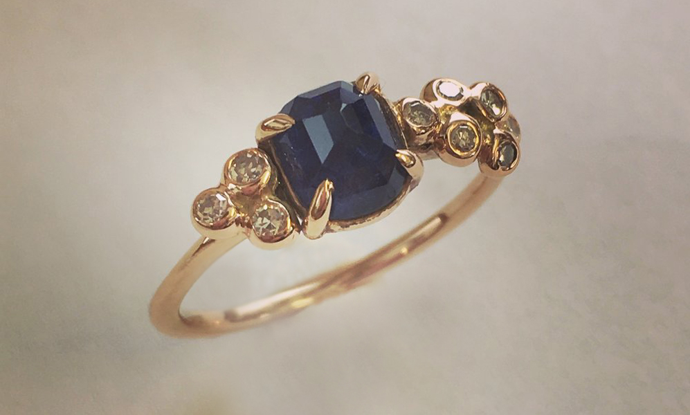 "9 Carat Rose Gold, Sapphire & Diamond Engagement Ring - One of our favourite 'up-cycle' and redesigns. This very pretty and unusual design was originally 'Pip's Grandmother's engagement ring. We transformed a once classic, Edwardian style engagement ring into an organic, contemporary design that 'Pip' felt truly spoke to her today. Carrying a piece of her Grandmother's heart and gemstones through more generations to come.""Rosie did a fabulous job on my engagement ring! My fiancé found her at a Brighton Open House and found out that she redesigned family heirlooms. We had a sapphire and diamond ring that I had inherited that had just sat unloved in a drawer for years. Rosie took my old heirloom and transformed it into the beautiful ring I wear everyday. She listened to my concerns and suggestions, and made my old ring into a fabulous, new and unusual ring that I would never have found on the high street. Rosie herself is a lovely lady and always happy to help. I look forward to her making my wedding ring! Pip."""