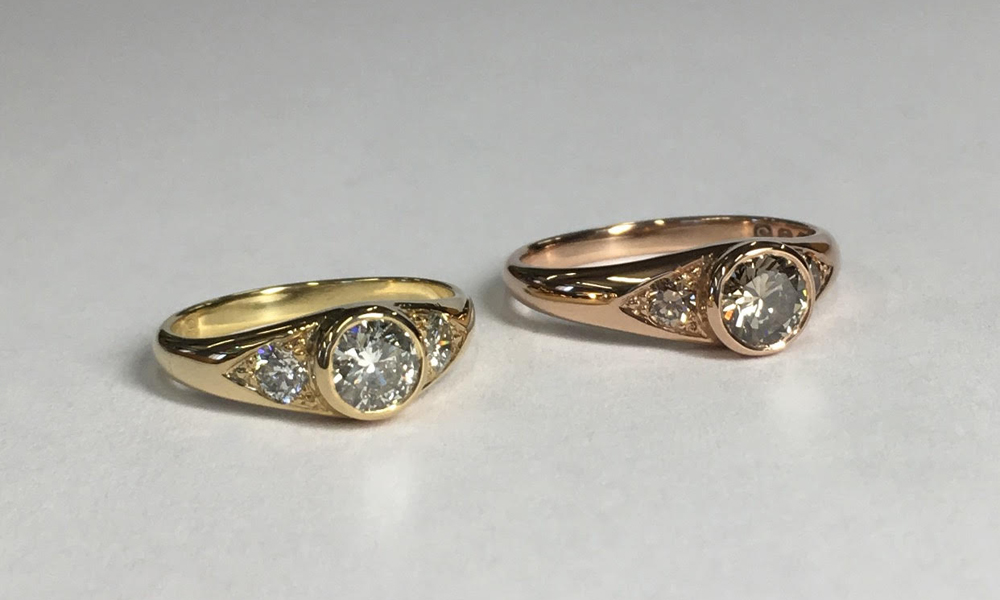 "18 Carat Yellow & Rose Gold&Grey Champagne Diamond Engagement Rings - Stunning and timeless 'Her's & Her's' engagement rings. Hand carved from wax and cast in yellow and rose gold gold. Set with grey and champagne diamonds, for that unique, vintage style sparkle.""I always loved the idea of designing an engagement ring and thrilled I got the opportunity to do this for myself and my partner. I wanted the rings to be bespoke and a matching pair but for each of them to also have their own personal touches. Rosie Odette was fantastic at guiding me (a complete novice) through the process. I showed her some images for inspiration; she then sketched some ideas in front of me for me to take away and consider. Our second meeting was set up to talk through choice of diamond and gold. Rosie would delicately place the diamonds on my fingers to show me the slight variations in colour and how they each worked with different types of gold. This was one of the most exciting parts of the whole process. Throughout the next couple of months, Rosie worked on the rings and sent me various images at different stages. She was a calming presence through what could have been a stressful process and delivered a stunning pair of engagement rings. It feels so special to have designed a ring for the person I love and know my (now) wife loves the sentiment behind the ring as much as the ring itself. Donna Xx"""